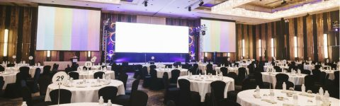 3 large screens with a projector for an event with round tables in the foreground, chairs draped in black.